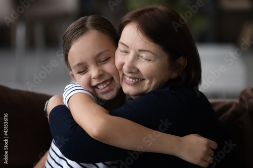 Fototapeta Loving mature grandmother and small teenage granddaughter hug cuddle show care and support in relations. Cute little teen girl child embrace elderly granny feel grateful thankful to grandparent. obraz