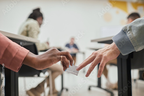 Foto Close up of two unrecognizable students passing cheat note while taking exam in