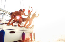 Side View Of Young Crazy Friends Jumping From Sailboat On Sea Ocean Trip - Men And Women Having Summer Fun Together At Sail Boat Party Day - Luxury Excursion Concept On Warm Backlight Filter