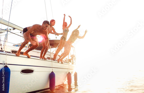 Canvastavla Side view of young crazy friends jumping from sailboat on sea ocean trip - Men a