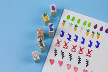 Easter Eggs. Easter Eggs Stamp. Drawing Of Carrots, Hearts, Rabbit, Hare, Branches. On A Blue Background. Handmade.