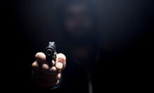 Holding A Gun On A Dark Background