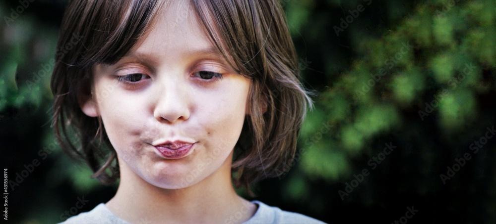 Fototapeta Mlody chlopiec, dłuższe włosy,  szary t-shirt, portret na zewnątrz, grymas na twarzy.