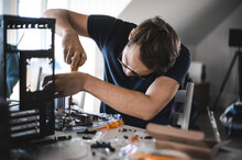 Portrait Of A Handsome Nerd Man Is Servicing Computer Motherboard And Cooler.