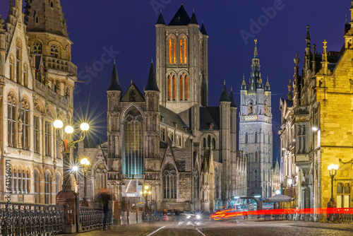 Foto Ghent (Gent) city center at night with blurred motion of people and transportation vehicles with Saint Bavo Cathedral and belfry, East Flanders, Belgium