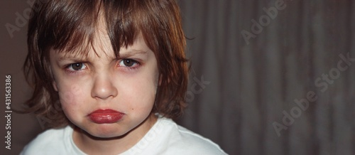 Obraz Chlopiec, przedszkolak, biały t-shirt. Portret twarzy, horyzontalny, zrobiony wewnątrz na szarym tle. Na twarzy wymalowany grymas, złość, gniew. - fototapety do salonu