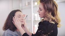 Makeup Artist Combs  Eyebrows In A Woman With An Eyebrow Brush. Make-up Artis