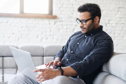 Fototapeta Serious multiracial man using laptop computer for remote work from home, hindu freelancer guy reading incoming emails, chatting online, researching or studying online sitting on the couch at home obraz