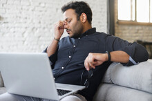 Tired Mixed-race Hindu Male Entrepreneur Take Glasses Off And Feel Eye Strain From Online Work With Laptop, Indian Man Sits On The Couch And Massaging Eyes, Feels Headache And Lack Of Energy