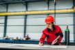canvas print picture Portrait of an engineer working on blueprint at industrial hall.