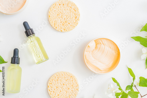 Obraz Flat lay composition with cosmetics and jasmine flowers on a light background - fototapety do salonu