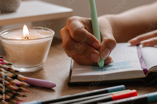 Obraz mano de mujer bocetando sobre cuaderno blanco ,  usando marcadores y lapiceros , decorado con colores cálidos madera y vela encendida. - fototapety do salonu