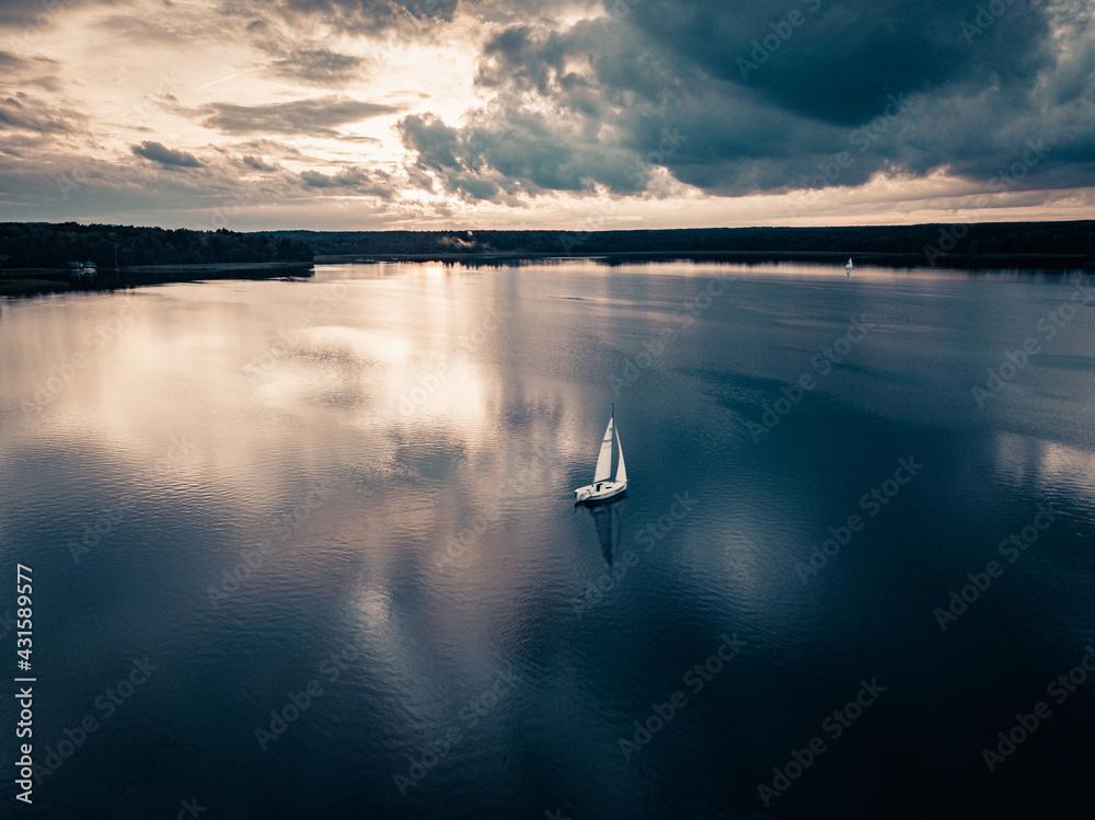 Żaglówka nad jeziorem z dramatycznym niebem