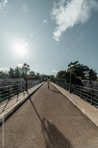 Kobieta spacerująca po moście w słoneczny dzień - fototapety na wymiar