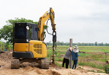 Workers Put Fence Posts Into The Pit Of The Excavator.