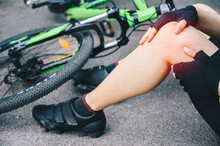 Cropped Shot Of Cyclist Woman Suffering From Knee Pain After Car Accident On The Road. Conceptual Of Accident Car Crash With Bicycle On Road.
