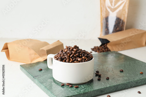 Obraz Cup with coffee beans on light background - fototapety do salonu