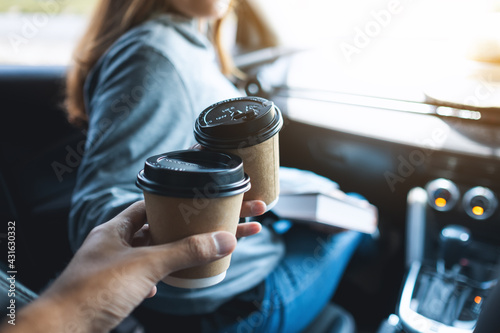Obraz Closeup image of a young woman holding a map and clinking coffee cup with friend while riding in the car - fototapety do salonu