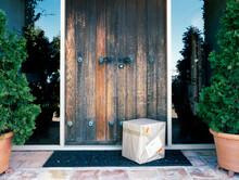 Parcel Delivered Outside Old Wooden Door Of Home