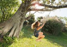 Teenage Girl Swinging On Rope Swing Tied To Big Old Tree