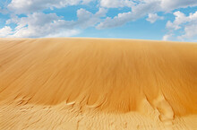 Looking Up At Golden Sand Dune With Blue Sky And Clouds Up Above