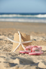 Flip Flops And Starfish Next To Sandcastle On The Beach