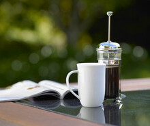 Cup And Magazine On Outdoor Table Setting