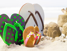 Flip Flops Standing Upright In The Sand Next To Sandcastles