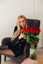 Attractive Blonde Model In Black Touching Red Roses.