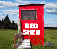 Old Public Phone Box Painted Red And Old Seat In The Middle Of Green Field