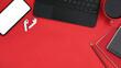Leinwandbild Motiv Mock up smart phone, keyboard, wireless earphone, coffee cup and notebook on red background. Top view.