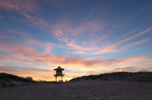 Looking Up From The Beach At Lone Lifeguard Tower At Sunset
