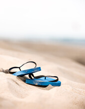 Blue Pair Of Flip Flops Abandoned On The Sand