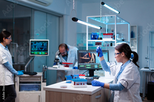 Fototapeta Team of scientific researchers working with professional modern equipment in laboratory. Chemists in pharmaceutical lab examining sample for medical experiment with technology for medicine industry. obraz