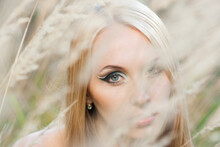 A Look Of A Blonde Girl Through Dry Grass In A Light Tone. Close-up. Selective Focus. Blurred Background.