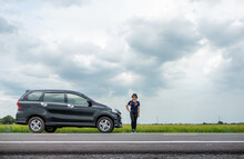 Female Tourist Standing With Arm Akimbo In Front Of Her Car. It Is Breaking Down At Roadside In Rural Area.