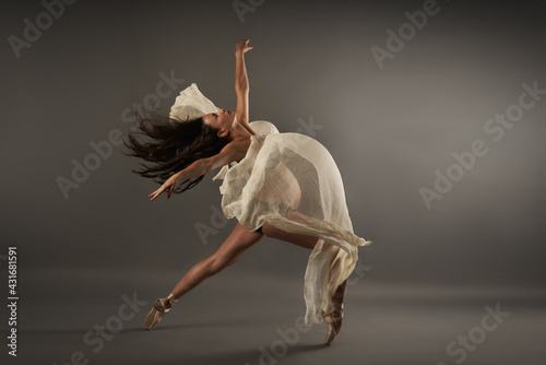 Young Hispanic pregnant ballerina performing classical ballet pose with a silk c Fototapet