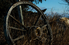 Selective Focus Shot Of An Old Wagon Wheel In A Field