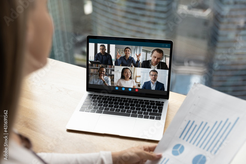 Fototapeta Female employee discuss paperwork with multiracial colleagues on video online call on laptop at home. Multiethnic diverse businesspeople talk speak on webcam zoom conference. Virtual event concept. obraz