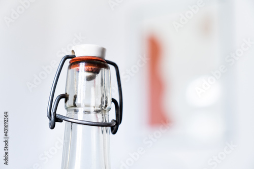 Obraz Une bouteille en verre transparent avec un bouchon refermable en capsule de porcelaine - fototapety do salonu