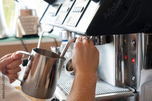 Obraz Barista whipping milk in metallic pitcher for cappuccino or latte - fototapety do salonu