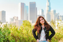 Young Beautiful Brunette Woman Stands With A View Of Downtown Skyscrapers In Los Angeles