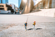 Miniature Figures Of People Tourists With Backpacks On Stand In Front Of The Walt Disney Concert Hall In Los Angeles