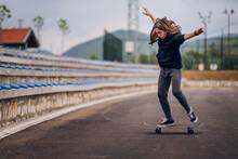 Teenage Girl Performing Skateboard Tricks On The Sports Field.