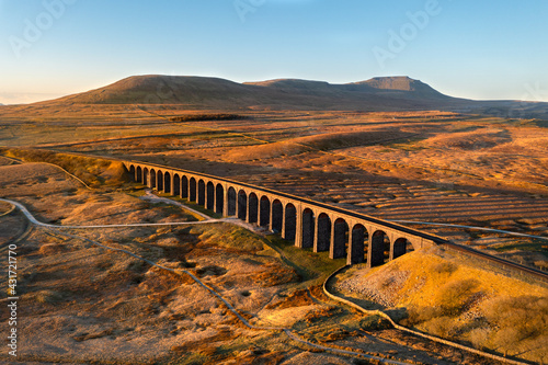 Golden morning light on Ribblehead Viaduct arches surrounded by wide open moorland Wallpaper Mural