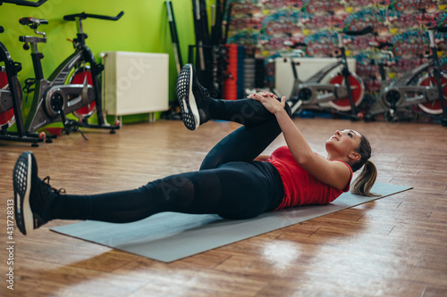 Fotografie, Obraz Young beautiful woman stretching in the gym
