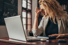Businesswoman Being Tired While Working On A Laptop In Her Office