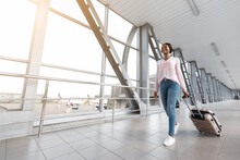 Happy African American Traveller Woman Walking With Luggage Suitcase In Airport Terminal