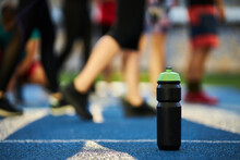 Close Up Black Sports Bottle With Green Cap Stands On A Blue Rubber Treadmill With A White Line. Water Sports Drink On The Background Of A Running Track With A Blue Rubber Coating With A White Line.
