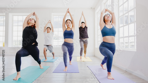 Naklejka premium Young Asian sporty attractive people practicing yoga lesson with instructor. Asia group of women exercising healthy lifestyle in fitness studio. Sport activity, gymnastics or ballet dancing class.